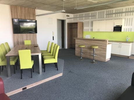 Besprechungsraum im Co-Working+ mit Sesseln, Tisch und Flatscreen im linken Bildteil, Küchenzeile mit Theke im rechten Bildteil.