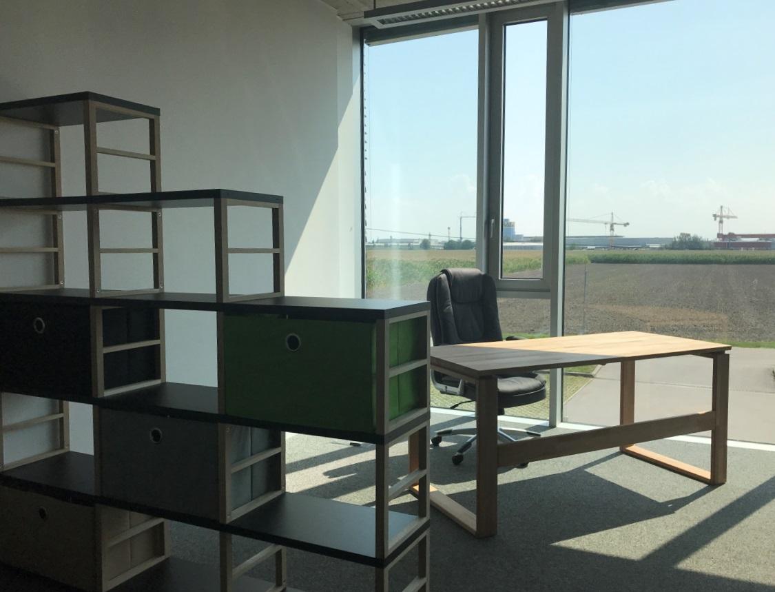 Arbeitsplatz mit REgal im Vordergrund. nebenbei Schreibtisch, Hintergrund Glasfront öffnet Blick auf Felder und Industriezoneerg