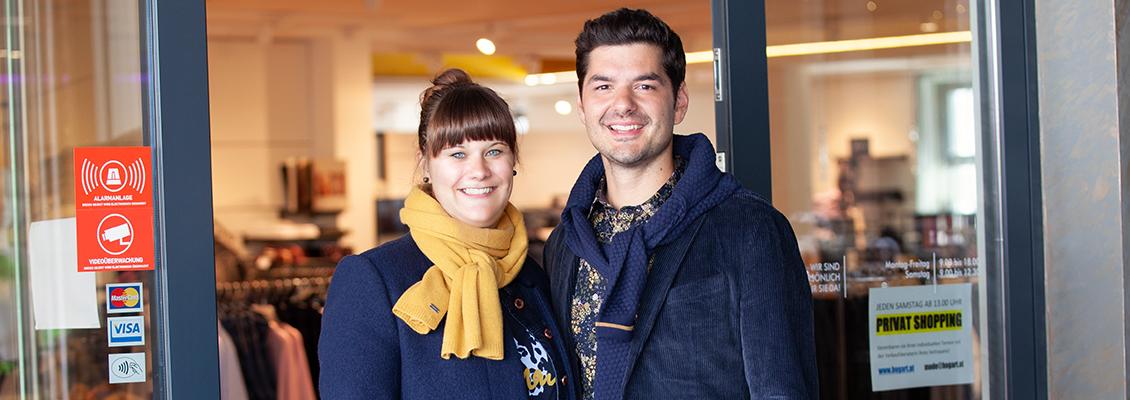 Frau und Mann vor Geschäftseingang