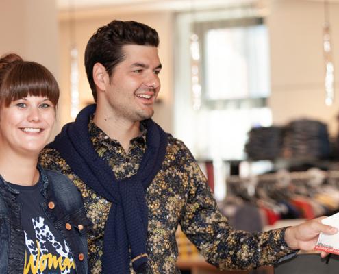 Frau und Mann an der Kassa bezahlen mit PERG-Gutschienen